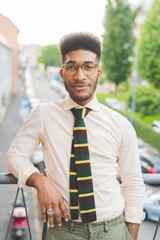 Jovem negro homem de negócios ao ar livre procurando câmera