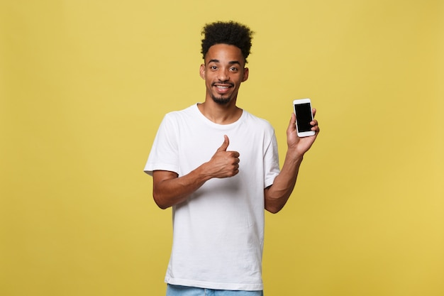 Jovem negro isolado em fundo amarelo, segurando o smartphone em branco