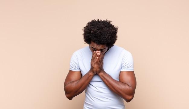 Jovem negro negro encolhendo os ombros, sentindo-se confuso e inseguro, duvidando com os braços cruzados e olhar perplexo