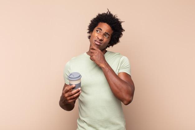 Jovem negro negro pensando, se sentindo duvidoso e confuso, com diferentes opções, se perguntando qual decisão tomar