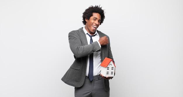 Jovem negro negro sentindo-se feliz, positivo e bem-sucedido, motivado para enfrentar um desafio ou comemorar bons resultados