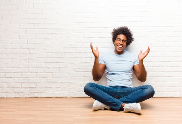 Jovem negro olhando feliz e animado, chocado com uma surpresa inesperada com as duas mãos abertas ao lado do rosto, sentado no chão em casa