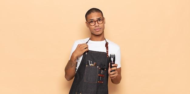 Jovem negro parecendo arrogante, bem-sucedido, positivo e orgulhoso, apontando para si mesmo
