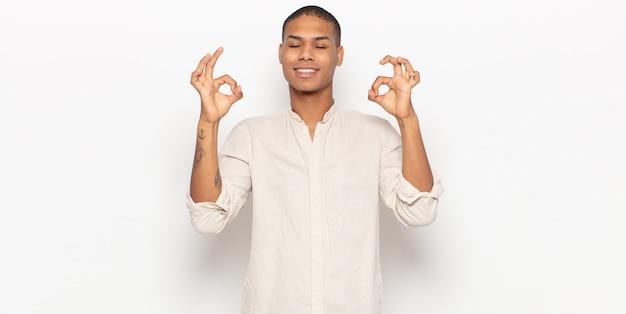Jovem negro parecendo concentrado e meditando, sentindo-se satisfeito e relaxado, pensando ou fazendo uma escolha
