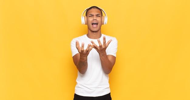 Jovem negro parecendo desesperado e frustrado, estressado, infeliz e irritado, gritando e gritando