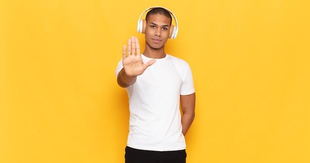 Jovem negro parecendo sério, severo, descontente e irritado mostrando a palma da mão aberta fazendo gesto de pare