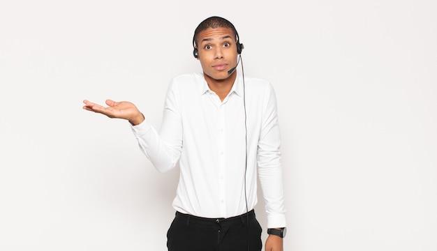 Jovem negro parecendo surpreso e chocado, com o queixo caído segurando um objeto com a mão aberta na lateral