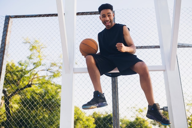 Jovem negro praticando esportes, jogando basquete, estilo de vida ativo, manhã de verão, sorrindo feliz se divertindo