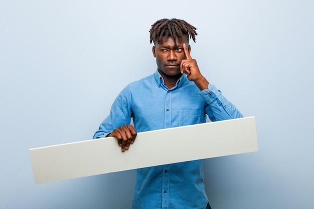 Jovem negro rasta segurando um cartaz apontando seu templo com o dedo, pensando, focado em uma tarefa.