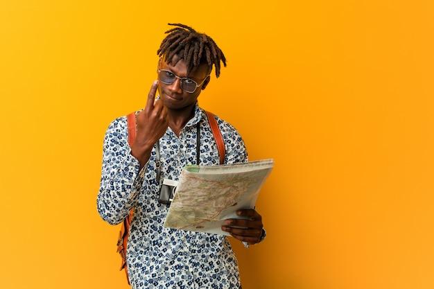 Jovem negro rasta segurando um mapa apontando com o dedo para você como se convidar se aproximar.