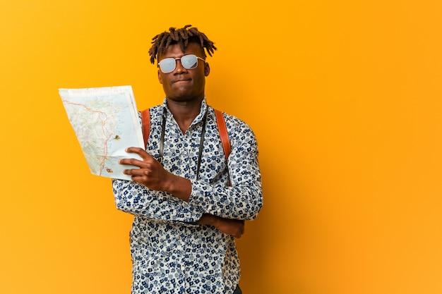 Jovem negro rasta segurando um mapa sorrindo confiante com braços cruzados.