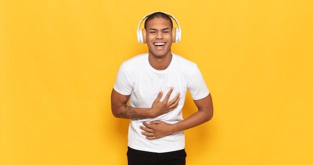 Jovem negro rindo alto de alguma piada hilária, sentindo-se feliz e alegre, se divertindo