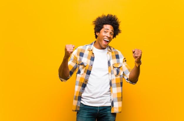 Jovem negro se sentindo chocado, animado e feliz, rindo e comemorando o sucesso, dizendo uau! contra parede laranja