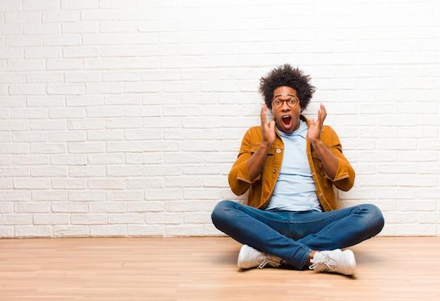 Jovem negro se sentindo chocado e animado, rindo, espantado e feliz por causa de uma surpresa inesperada sentada no chão em casa