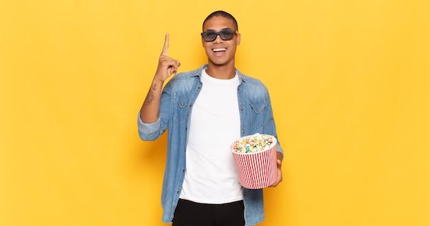 Jovem negro se sentindo um gênio feliz e empolgado depois de realizar uma ideia, levantando o dedo alegremente, eureka!