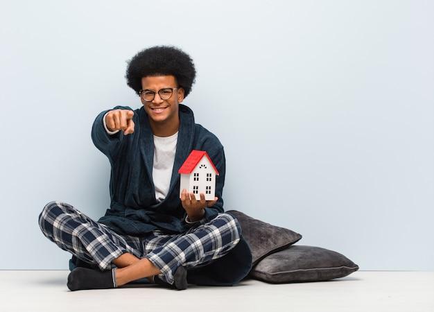 Jovem negro segurando um modelo de casa, sentada no chão, alegre e sorridente, apontando para a frente
