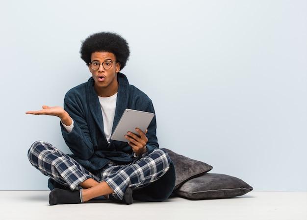 Jovem negro sentado em sua casa e segurando seu tablet segurando algo na mão da palma