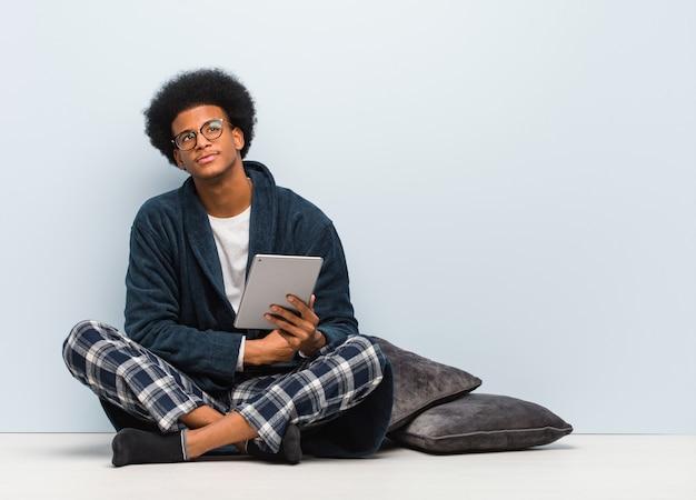 Jovem negro sentado em sua casa e segurando seu tablet sorrindo confiante e cruzando os braços, olhando para cima