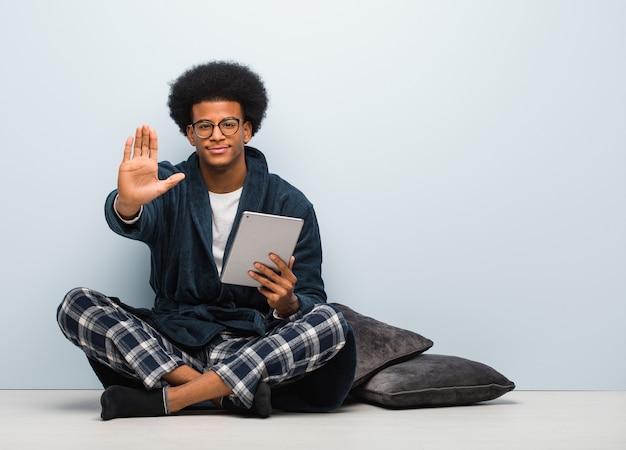 Jovem negro sentado em sua casa segurando seu tablet e colocando a mão na frente
