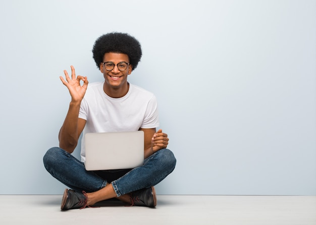 Jovem negro sentado no chão com um laptop alegre e confiante, fazendo o gesto de ok