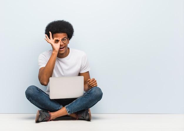 Jovem negro sentado no chão com um laptop confiante fazendo um gesto de ok no olho