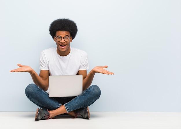 Jovem negro sentado no chão com um laptop duvidando e dando de ombros
