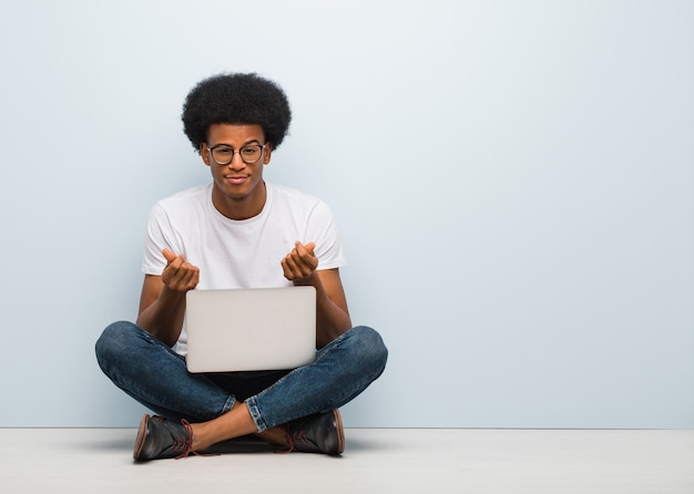 Jovem negro sentado no chão com um laptop, fazendo um gesto de necessidade