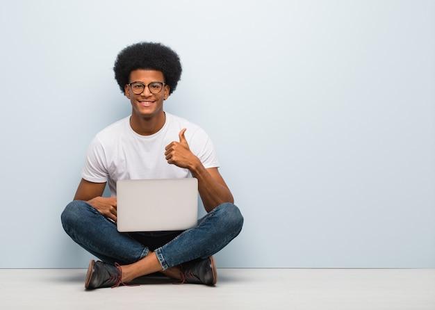 Jovem negro sentado no chão com um laptop sorrindo e levantando o polegar para cima
