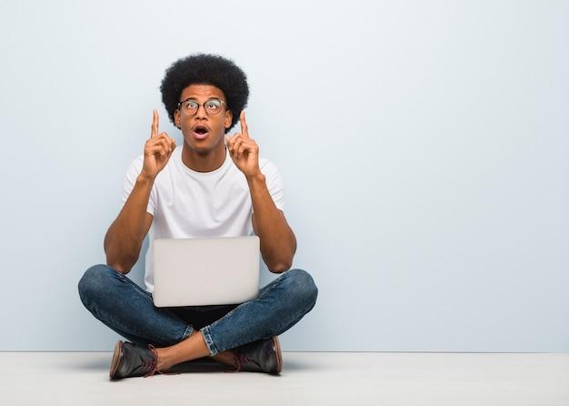 Jovem negro sentado no chão com um laptop surpreso apontando para cima para mostrar algo