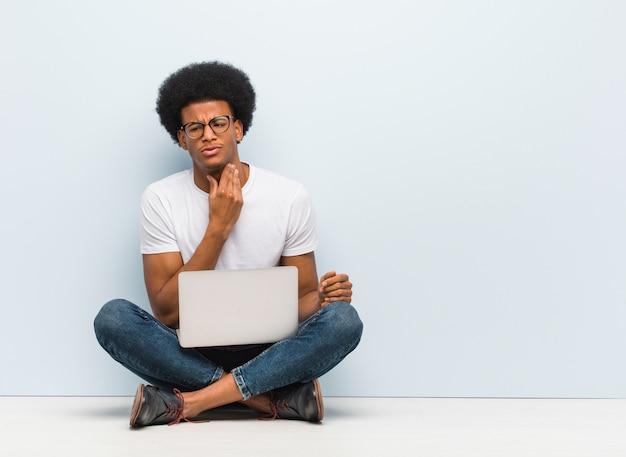 Jovem negro sentado no chão com um laptop tossir, doente devido a um vírus ou infecção