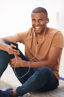Jovem negro sentado no chão e ouvindo música no telefone inteligente