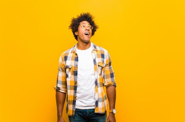 Jovem negro sentindo chocado, feliz, espantado e surpreso, olhando para o lado com a boca aberta na parede laranja
