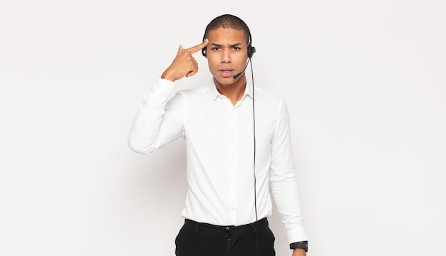 Jovem negro sentindo-se confuso e perplexo, mostrando que você é louco, louco ou maluco