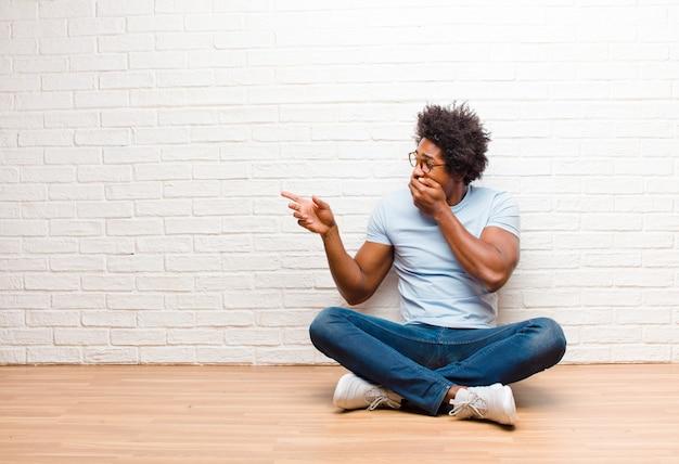 Jovem negro, sentindo-se feliz, chocado e surpreso, cobrindo a boca com a mão e apontando para o espaço lateral da cópia, sentado no chão em casa