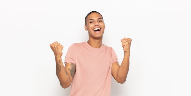 Jovem negro sentindo-se feliz, positivo e bem-sucedido, comemorando a vitória, conquistas ou boa sorte