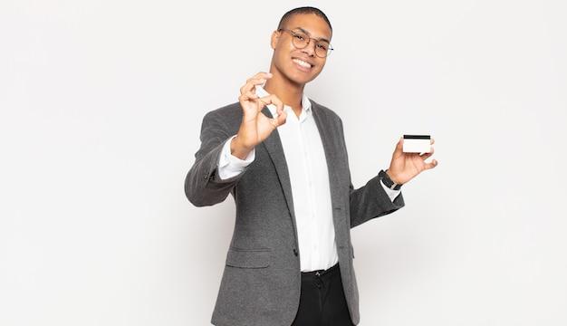 Jovem negro sentindo-se feliz, relaxado e satisfeito, mostrando aprovação com gesto de ok, sorrindo