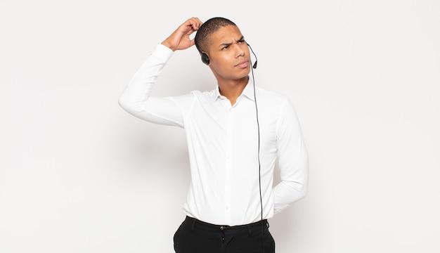 Jovem negro sentindo-se perplexo e confuso, coçando a cabeça e olhando para o lado