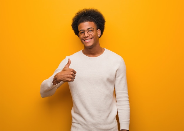Jovem negro sobre uma parede laranja, sorrindo e levantando o polegar