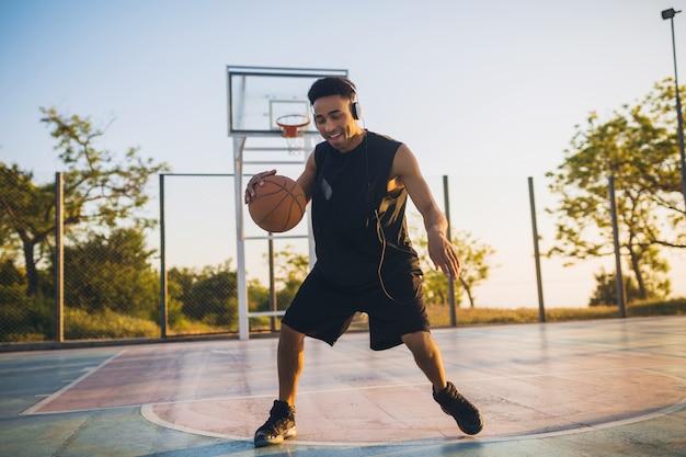 Jovem negro sorridente e feliz praticando esportes, jogando basquete ao nascer do sol, ouvindo música em fones de ouvido, estilo de vida ativo, manhã de verão