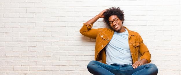 Jovem negro sorrindo alegre e casualmente, levando a mão à cabeça com um olhar positivo, feliz e confiante, sentado no chão em casa