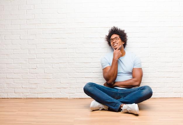 Jovem negro sorrindo alegremente e sonhando acordado ou duvidando, olhando para o lado sentado no chão em casa
