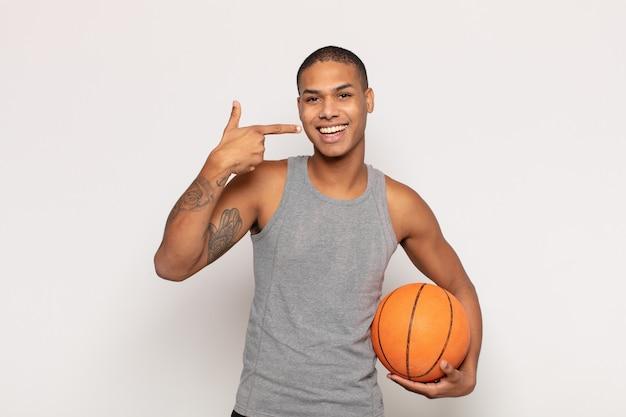 Jovem negro sorrindo com confiança apontando para seu próprio sorriso largo, atitude positiva, relaxada e satisfeita