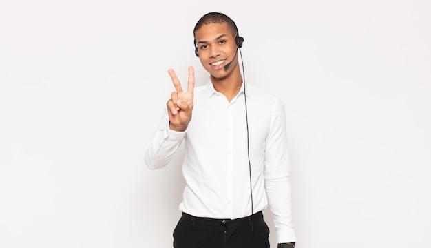 Jovem negro sorrindo e parecendo amigável, mostrando o número dois ou o segundo com a mão para a frente, em contagem regressiva