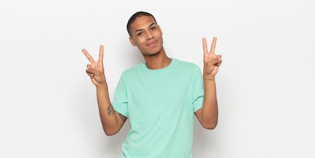 Jovem negro sorrindo e parecendo feliz, amigável e satisfeito, gesticulando vitória ou paz com as duas mãos