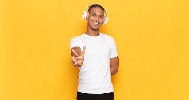 Jovem negro sorrindo e parecendo feliz, despreocupado e positivo, gesticulando vitória ou paz com uma das mãos