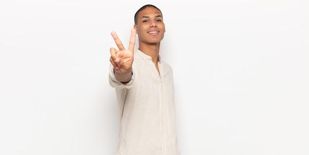 Jovem negro sorrindo e parecendo feliz, despreocupado e positivo, gesticulando vitória ou paz com uma mão