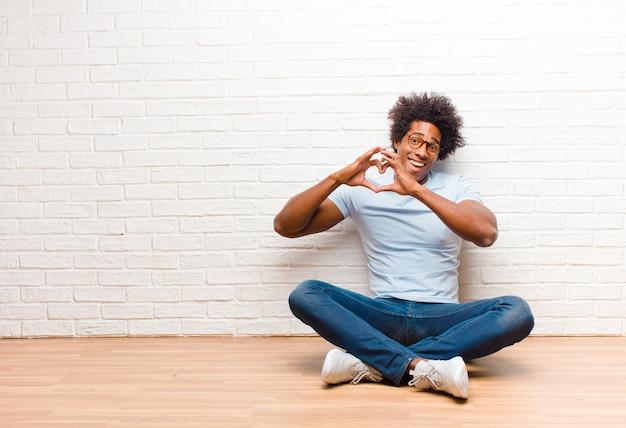 Jovem negro sorrindo e se sentindo feliz, fofo, romântico e apaixonado, fazendo formato de coração com as duas mãos, sentada no chão em casa