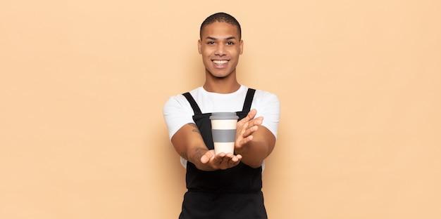 Jovem negro sorrindo feliz com um olhar amigável, confiante e positivo, oferecendo e mostrando um objeto ou conceito