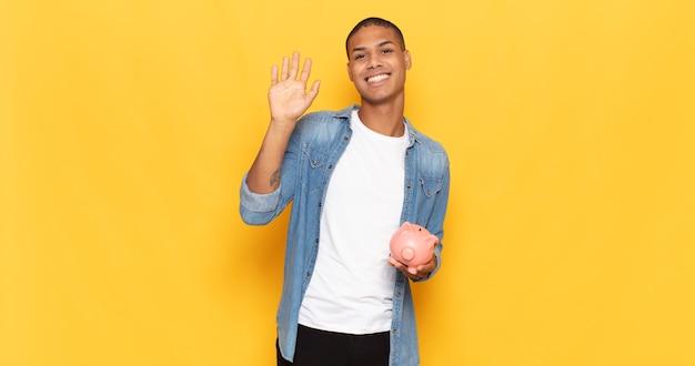 Jovem negro sorrindo feliz e alegre, acenando com a mão, dando as boas-vindas e cumprimentando ou dizendo adeus