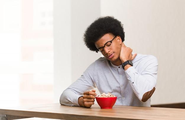 Jovem negro tomando um café da manhã com dor no pescoço